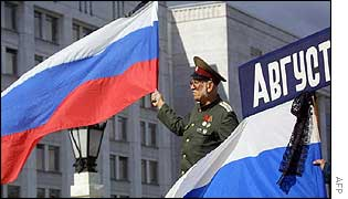 An officer holds the national flag of Russia in front of the Government House