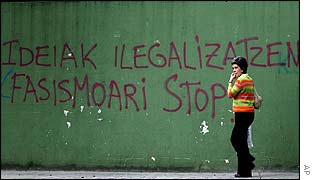 Passer-by walks past a wall painting which says (in Basque)  'Ban on ideas, stop fascism', in Tolosa, northern Spain