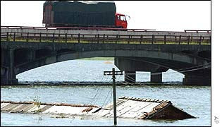 Lorry passes over a bridge above a flooded river