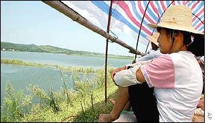 Locals watch a dyke on a flood river feeding Dongting