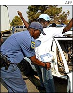 South African policeman searches a driver at a roadblock in Johannesburg