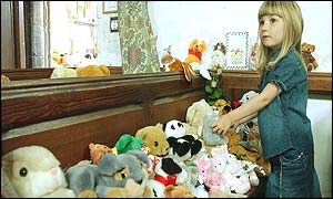 Child looks at the array of toys on a church bench