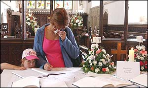 Woman signs book of condolence in St Andrews Church