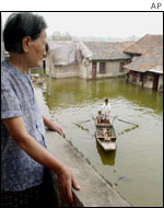 A woman looks out over a flooded building from a balcony in Huarong, Hunan Province