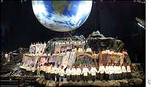 Choir performs under an image of the globe