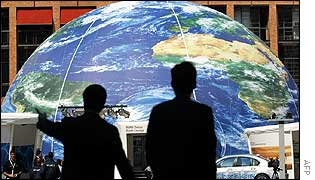 Delegates walk in front of a giant globe in Sandton Square