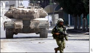 An Israeli soldier and patrolling tank in Nablus on Monday