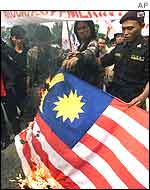 Indonesian protesters burn a Malaysian flag during a demonstration outside the Malaysian embassy in Jakarta