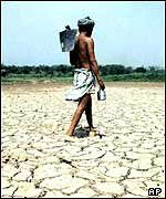 An Indian farmer walking across a dried out lake