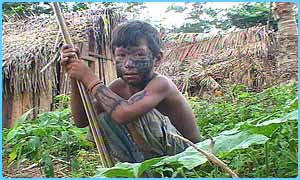 Tamata'i, 9, helps his father hunt for food in the forest