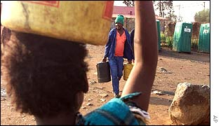 Residents of the Johannesburg suburb of Kliptown carry drinking water
