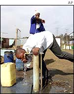 People collect water at a communal taps at a settlement in Soweto