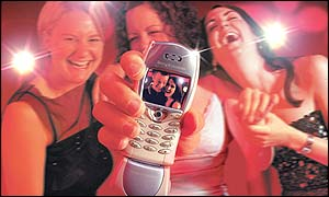 Women in a nightclub with a mobile phone and picture message