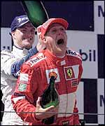 Ralf Schumacher pours champagne down Michael Schumacher's neck