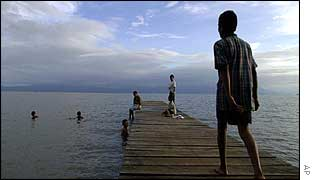 Children playing in Izabal Lake, Guatemala, which is rapidly becoming polluted