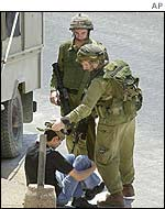 Soldiers with a detained Palestinian
