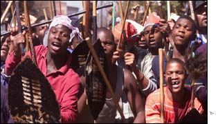 Some of 1,000 Zulu workers carrying sticks and traditional weapons march through the city centre