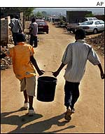 South African youths carrying water bucket