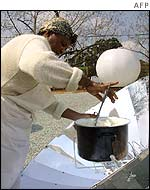 A woman cooks using a solar oven