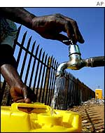 A woman collects water at a Johannesburg settlement