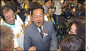 Yasuo Tanaka is greeted by supporters following his victory
