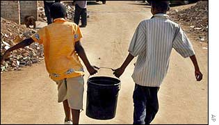 Children carrying water outside Johannesburg