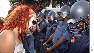 Protester faces South African police officers