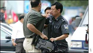 A Chinese policeman blocks a journalist