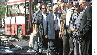 Sharon visiting the scene of a suicide bombing in June