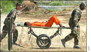 A prisoner is carried on a stretcher by two US soldiers at Guantanamo Bay