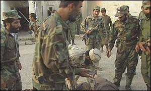 Afghan soldiers stand over the bodies of the assailant, one of Karzai's bodyguards and a third man