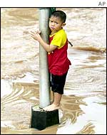 A Thai boy clings to a road sign amid floodwaters in Loei Province