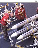 Ordnance men make ready ordnance for fighter jets on the USS George Washington aircraft carrier in the Persian Gulf