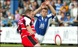 Bridgend scrum-half Huw Harries charges down Gary Armstrong's kick to score against Borders