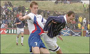 Scotland's Allan Johnston fights to keep the ball as the Faroe Islands press forward