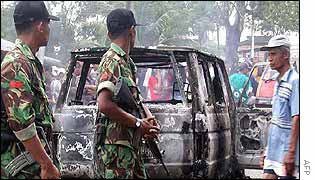 Soldiers stand guard beside a torched van