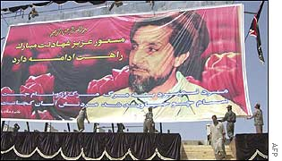 Afghan workers display a huge portrait of Ahmad Shah Masood at the sports stadium in Kabul