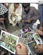 A group of Afghans look at photos of Masood