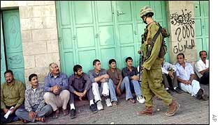 An Israeli soldier watches Palestinian suspects in Hebron