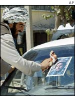 A fighter wipes his windshield bearing a portrait of Masood in Mazar-e-Sharif, northern Afghanistan