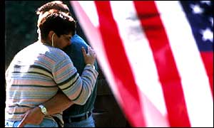 Couple embrace in front of US flag