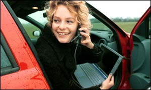 Presenter Kate Humble of BBC WebWise (1999) sits in a car using the internet with a laptop and mobile phone