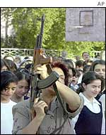 An Iraqi teacher fires an AK-47 to mark the beginning of school