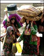 Afghan refugee women carry their belongings