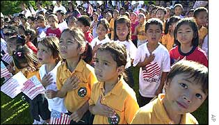 Children watch as the US flag is raised in Guam