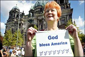 A woman holds a poster in front of the Berlin Dom cathedral