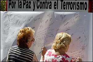 Spaniards write message on a large poster in Madrid; banner reads 'For Peace and Against Terrorism'