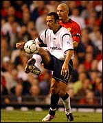 Bolton's Youri Djorkaeff maintains possession despite close attention from Rio Ferdinand of Manchester United