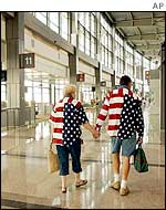 Passengers in patriotic colours make their way past empty gates at Austin Bergstrom International Airport, 11 September 2002