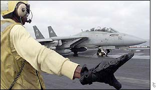 An aircraft director gives directions to the pilot of an F-14 on the flight deck of the USS George Washington aircraft carrier in the Arabian Sea